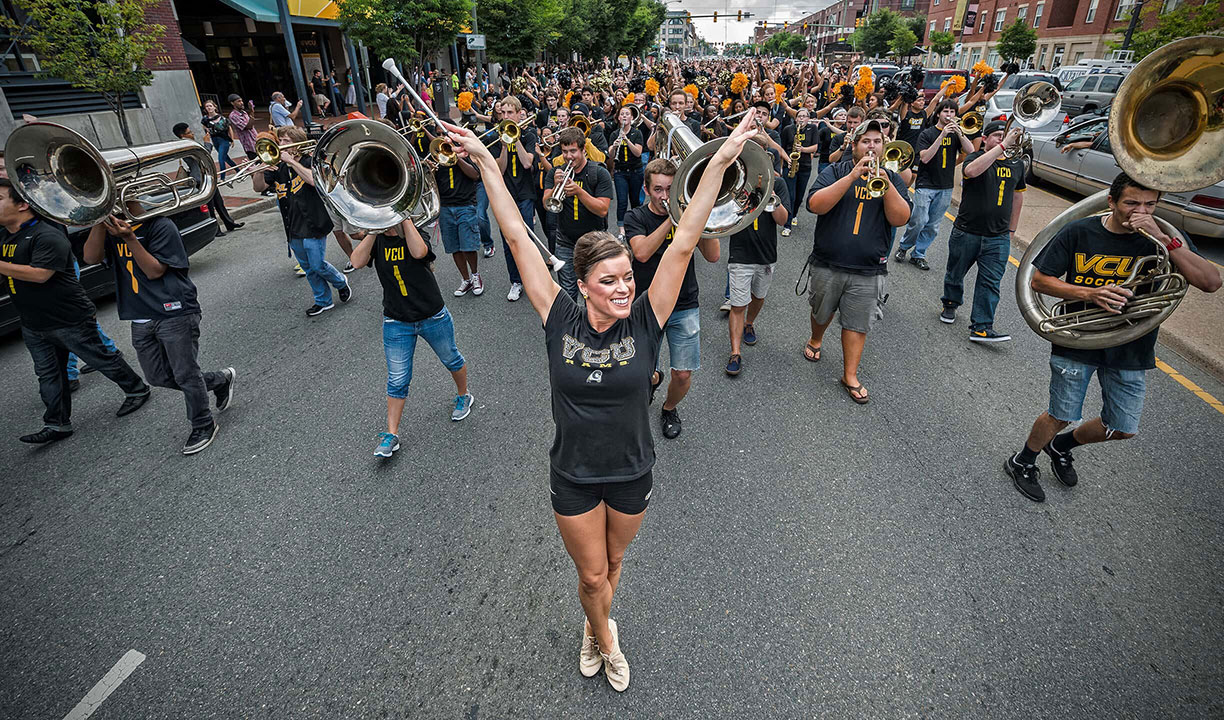 The VCU pep band leads a parade down the street
