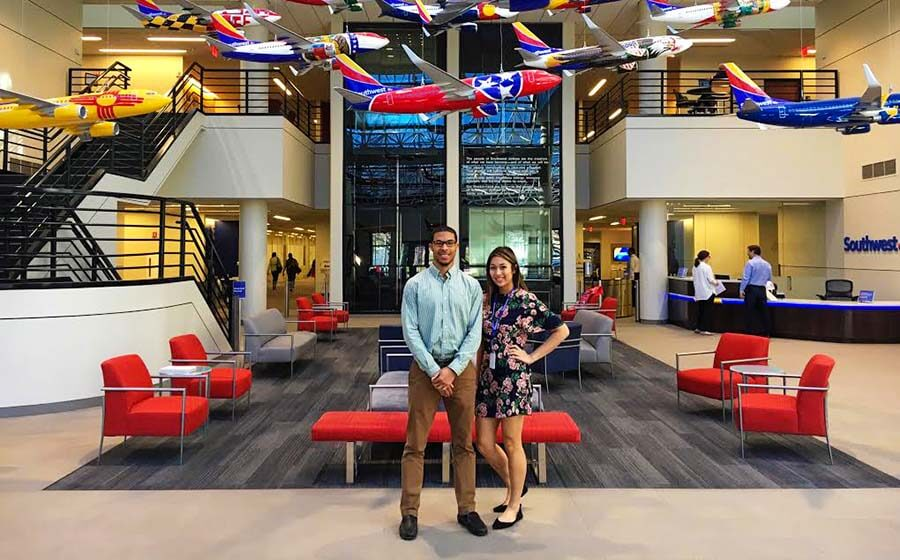 Man and woman standing in colorful lobby with model airplanes hanging overhead