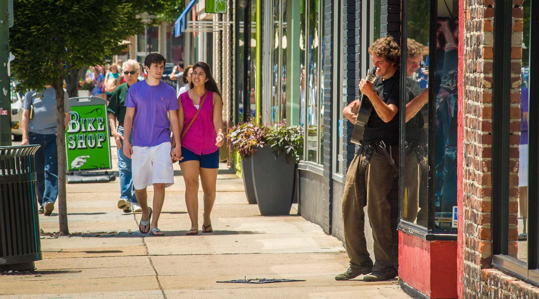 Pedestrians walk past a musician playing guitar on Cary St.