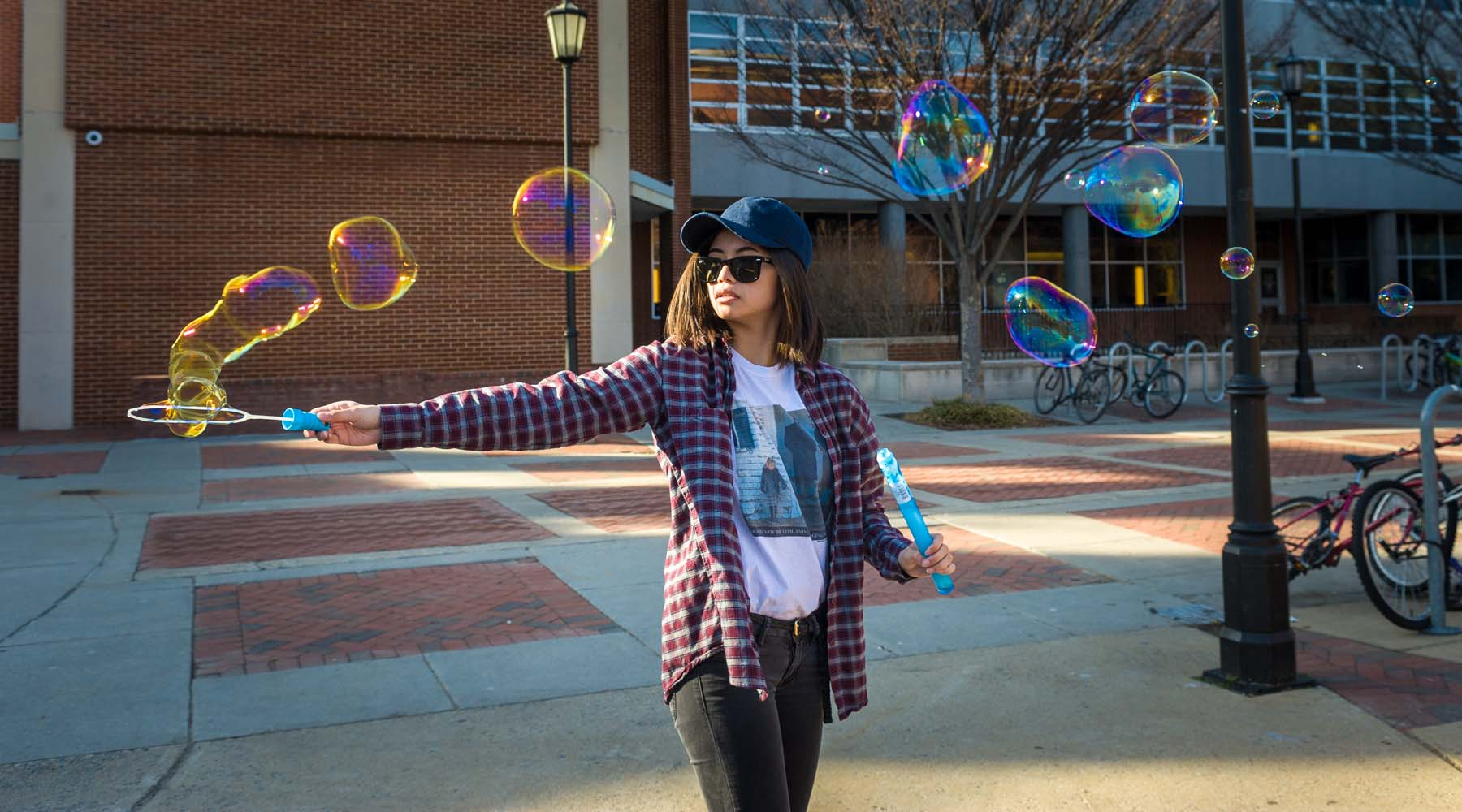 Student waving bubble wand in Shafer Court