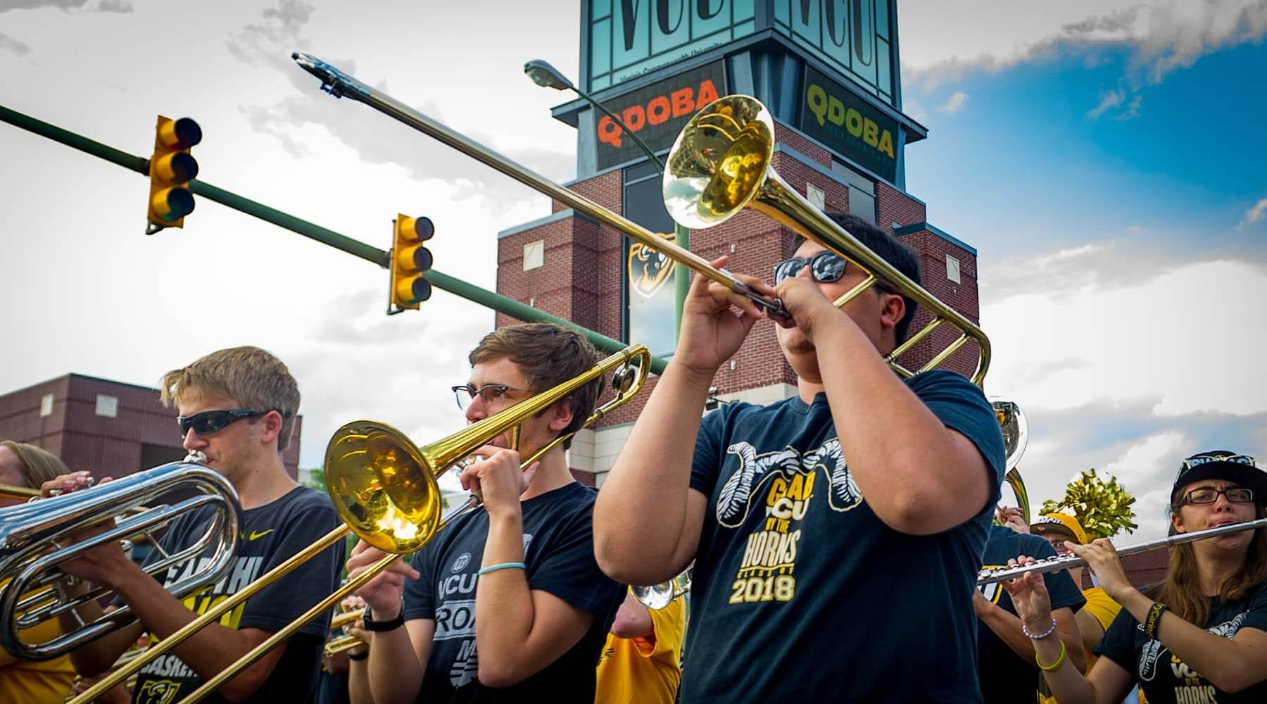 Members of VCU's pep band play their instruments as they march down Broad St.