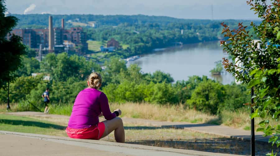 Woman sitting in park looking at view of James River