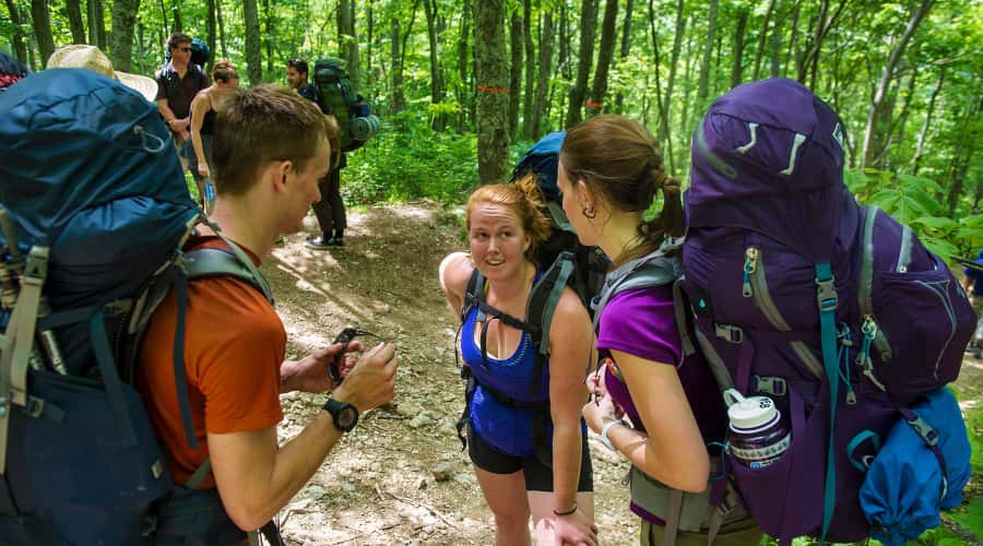 Students in woods wearing hiking backpacks